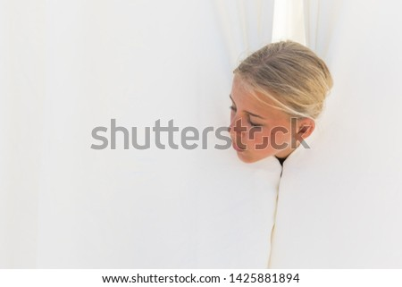 girl looks to the side and looks out from behind white curtains. Copy space for advertise.