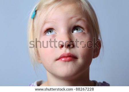 girl looks upwards and thinks