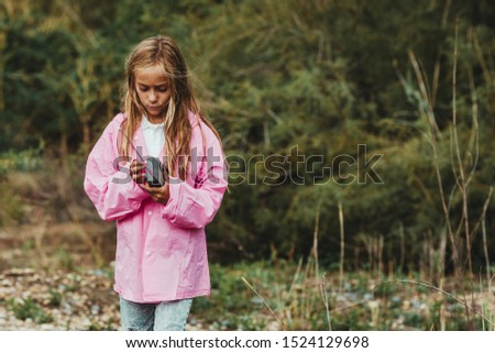 girl lost in the forest on a rainy day trying to communicate by gps with her gps phone #1524129698