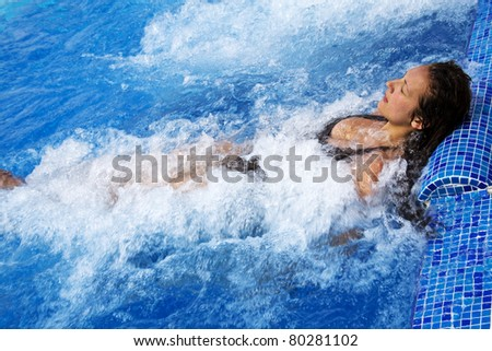 Girl lying in a pool with jacuzzi