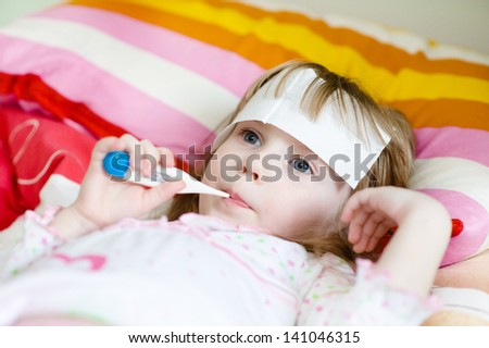girl lying in bed with a thermometer