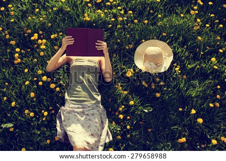 Girl lying in grass, reading a book. Intentionally toned.