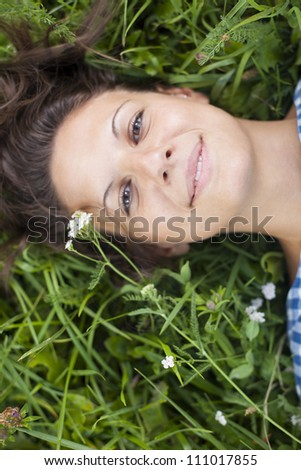 girl lying on a lawn - focus on smile