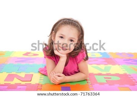 Girl lying on colorful mat resting head on hand. Isolated on white