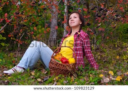 Girl lying on grass near basket of vegetables - stock photo