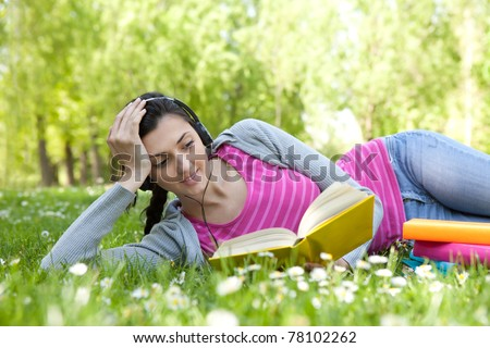 girl lying on grass with flower in park, reading  book and listening music through headset