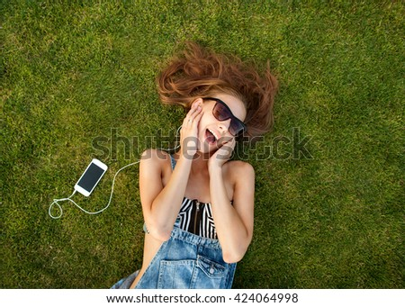 girl lying on the green grass, listening to music