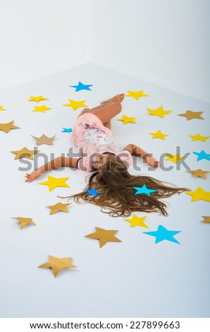 girl lying on the stars in the studio on a white background. Large colored paper stars. The magic of your own hands