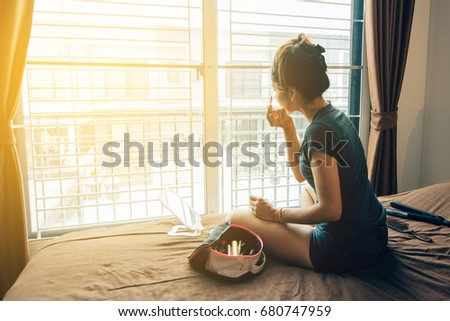 Girl make up in the bedroom, using natural light to enter through the curtain window #680747959