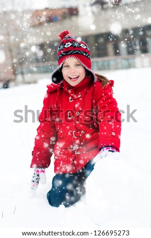 Girl makes a snowman outside in winter time