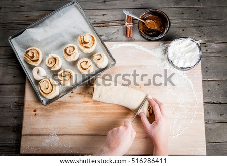 Girl makes homemade cinnamon buns, sliced rolls of dough roll. View from above, hands in picture