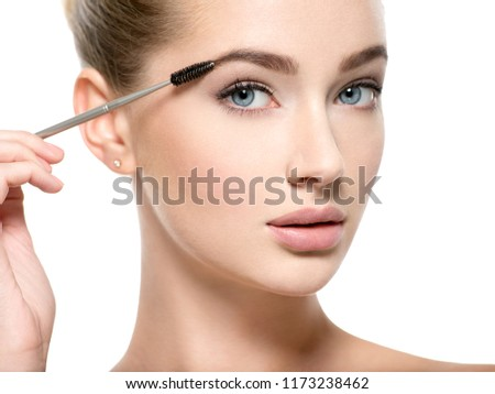 Girl makes makeup. Beautiful woman apply mascara on eyelashes  with cosmetic brush - isolated on white