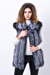 Girl makeup face long hairstyle wear fur vest white background. Luxury fur accessory. Fashion trend concept. Boutique selling fur. Winter fashionable wardrobe. Silver fur vest fashion clothing.