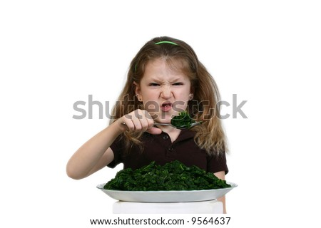 Girl making a disgusted face while eating spinach