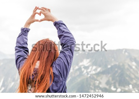 Girl making a heart-shape with mountain landscape in the background. Copyspace. A young pretty redheaded woman standing on a background of mountains. Trekking, vacation and tourism concept. Copyspace