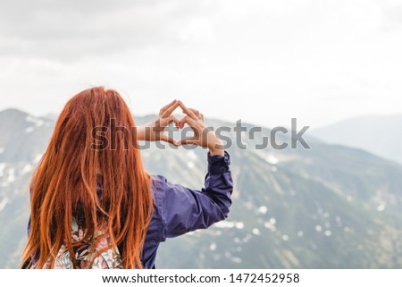 Girl making a heart shape with mountain landscape in the background. Copyspace. A young pretty redheaded woman standing on a background of mountains. Trekking, vacation and tourism concept. Copyspace