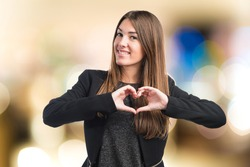 Girl making a heart with her hands on unfocused background
