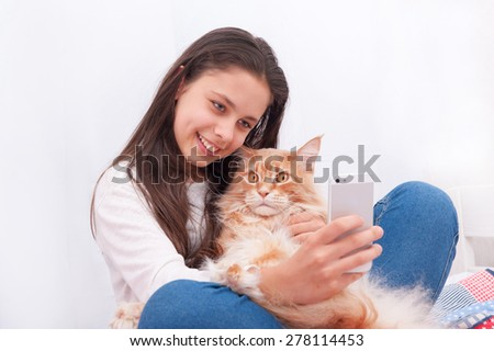 Girl making a photo with Maine Coon cat. Cat is very surprised