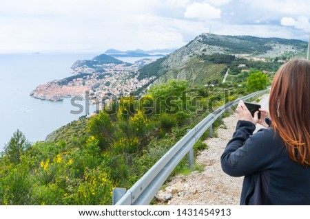 Girl Making pictures from Dubrovnik on the hill with a smart phone in a small road to the Old town in Croatia