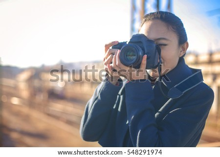 Girl making pictures with camera outside in the city