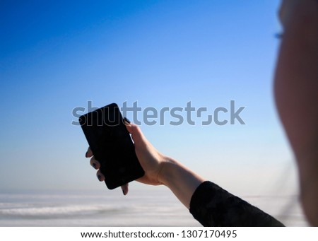 Girl making selfie on front camera of modern smartphone with seascape on the background. First person view. Girl holding mobile phone with blank mock up screen area on the sea shore. Screen view