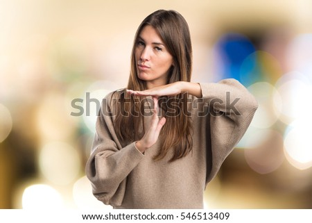 Girl making time out gesture on unfocused background