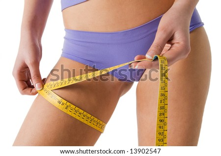 Girl measuring her thigh checking the result of diet, isolated on a white background