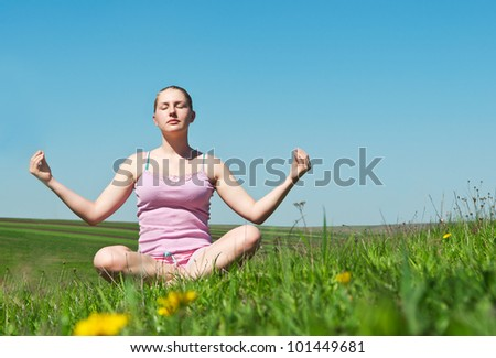 girl meditates in green grass background