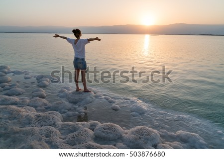 Girl meets sunrise on the shore the Dead Sea in Israel #503876680
