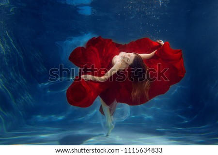 Girl mermaid. Underwater scene. A woman, a fashion model in the water in a beautiful dress swims like a fish. #1115634833