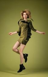 Girl, model in a beautiful dress in the studio in motion. Fashion, style, beauty.