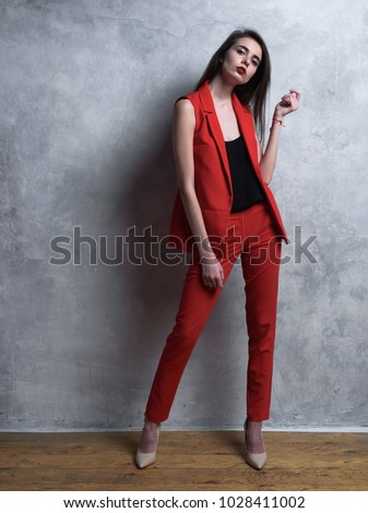 girl model in a red suit against a gray background. Studio photography. #1028411002