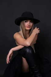 girl model in dark clothes and hat posing on black background studio