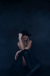 Girl model in dark dress and hat posing on black background