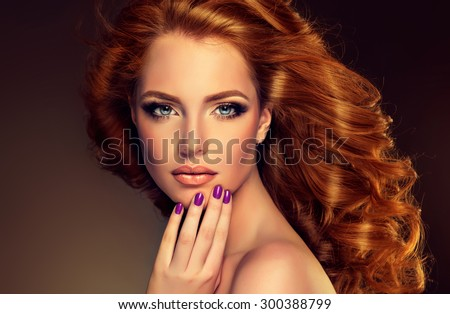 Girl model with long curly red hair . Trendy image  red head woman and purple nails