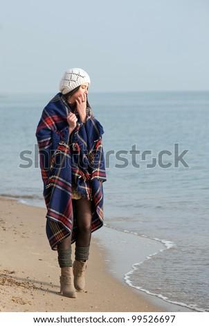 Girl muffled in a plaid walking the seaside
