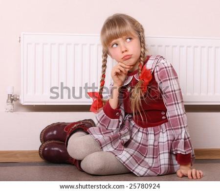 Girl near radiator. Energy crisis.