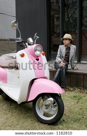 Girl next to her pink scooter (focus on bike)