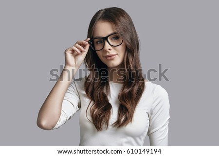 24ed0cd8eae Girl of your dreams. Attractive young woman adjusting her thick rimmed  glasses and looking at · Sunglasses concept.