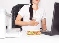 Girl office worker near which lies a sandwich holding on to a stomach in which there is pain and inflammation in the stomach. Concept of indigestion and malnutrition in office workers, gastritis and
