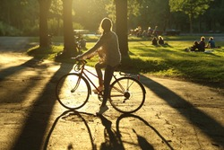 Girl on a bicycle in a park with the sun setting in behind her and behind trees. She is silhouetted with a long shadow.  People sit on grass blurred in the background and there is slight lens flare.
