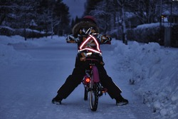 Girl on a bicycle in a winter evening. Light is reflected from clothing reflectors and bicycle wheels. Safe cycling in the dark time.