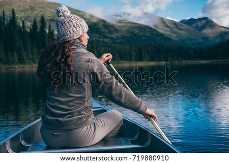 girl on a canoe is in awe with...