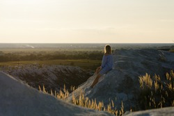 Girl on a mountain in a blue dress watches the sunset