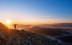 Girl on a mountain top with outstretched arms. Dramatic landscape of a lone hiker looking at mountains in fog at sunrise. Freedom, active lifestyle and victory concept.