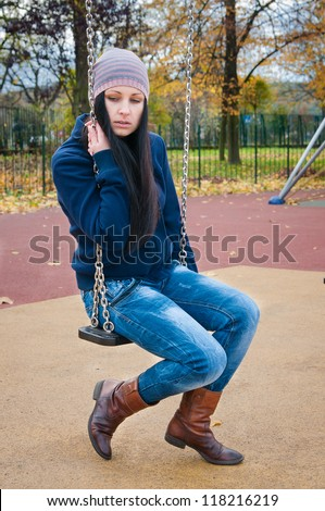 girl on a swing in the autumn park