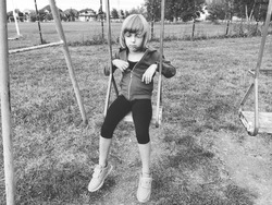 Girl on a swing. Monochrome retro photography. A child in a sports uniform is swinging. In the background is the stadium. Sadness on the face. The emotion of frustration and the feeling of loneliness.