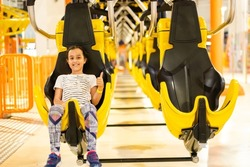 Girl on a thrilling roller coaster ride at an amusement park with arms raised and yelling with excitement
