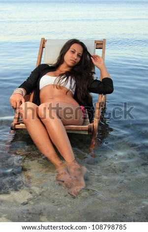 Girl on a tropical beach sitting on a sunbed in the evening