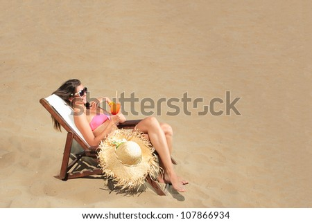 Girl on a tropical beach with hat and sunglasses holding a cocktail